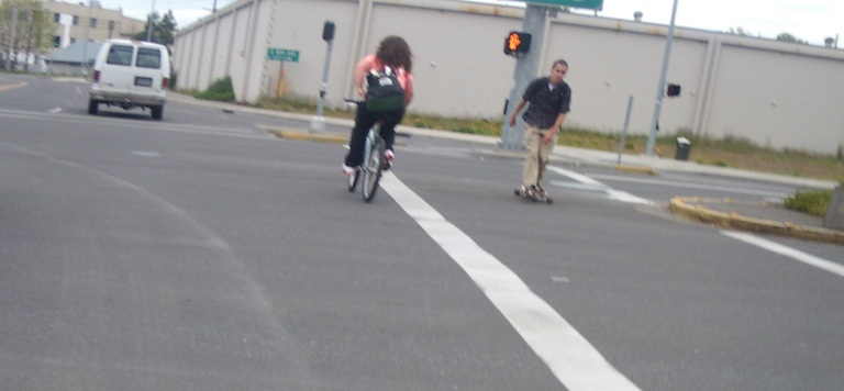 Skateboarder and cyclist meet in the crosswalk at Broadway and Hilyard in Eugene