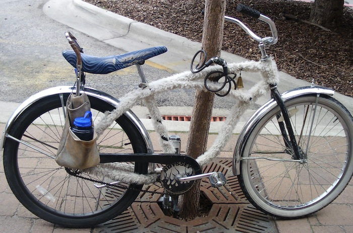 Bicycle covered in fur with carpenter belt pannier