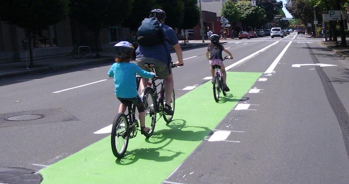 Family rides in a green bike lane