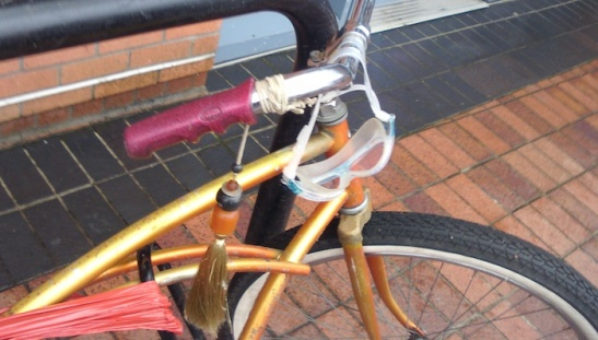 Goggles hanging off of a bicycle handlebar