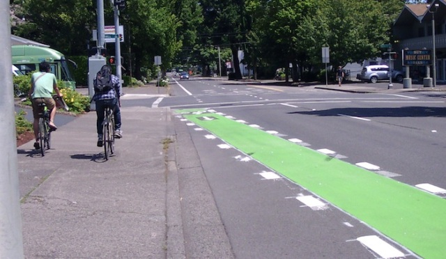 Cyclists riding on the sidewalk near a green bike lane