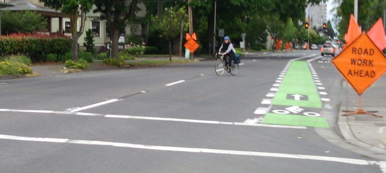 Woman on bicycle mispositioned along a green bike lane