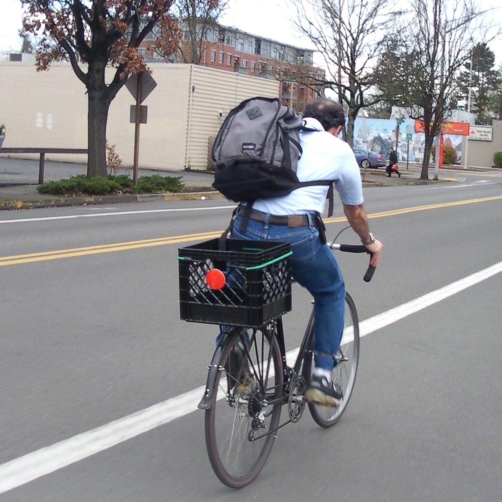 Man riding crate bike with big backpack