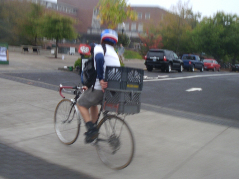 A cyclist on a crate bike carrying a secon crate