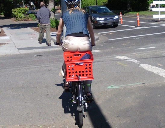 Buns hanging over into a bicycle mounted milk crate