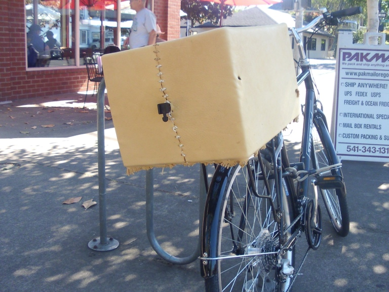 Bicycle with a milk crate covered in leather, with fringe