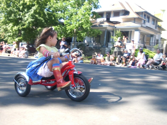 Photo of a girl on a tricycle in the Eugene Celebration Parade