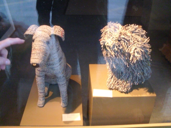 Photo showing dog sculptures that are made from twisted pieces of newspaper.