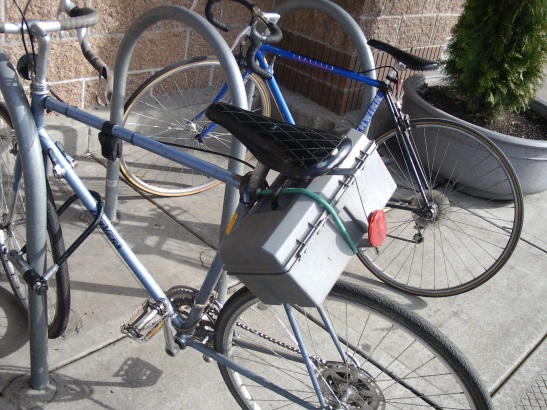 A small plastic toolbox used as a bike cargo hold